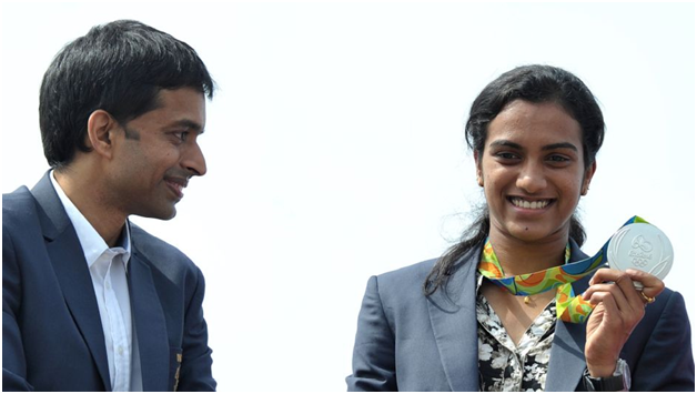 P. V. Sindhu with coach P. Gopichand and her silver medal from the 2016 Rio Olympics