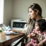 Mother Multi Tasking With Infant Daughter In Home Office